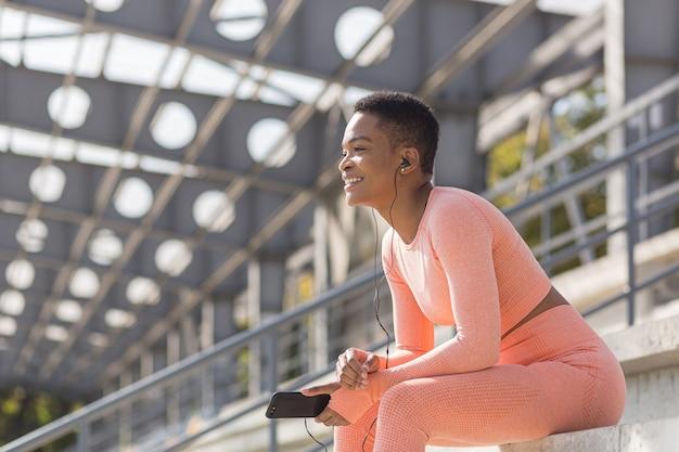 Schöne und erfolgreiche sportlerin, die lächelt, hört während der morgendlichen fitness und beim joggen in der nähe des stadions ein hörbuch vom handy, afroamerikanische frau mit handy