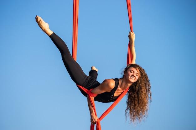 Schöne und flexible weibliche zirkusartistin, die mit luftseide auf einem himmelhintergrund tanzt.