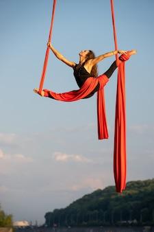 Schöne und flexible zirkusartistin, die mit luftseide auf himmelshintergrund tanzt.