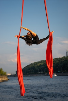 Schöne und flexible zirkusartistin, die mit luftseide mit himmel und flussküste tanzt