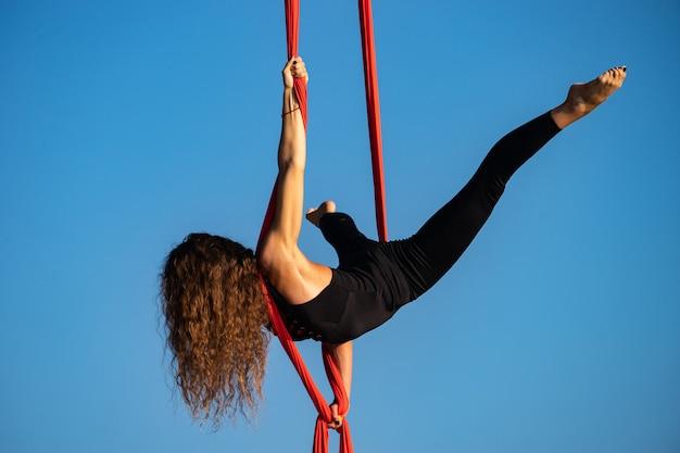 Schöne und flexible zirkusartistin, die mit luftseide tanzt