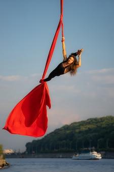 Schöne und flexible zirkusartistin tanzt mit luftseide mit himmel und flussküste im hintergrund.