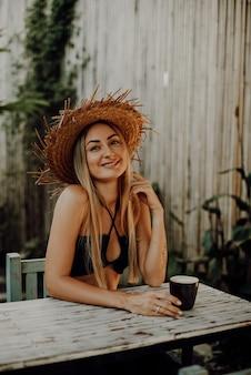 Schöne und fröhliche frau mit gebräunter haut und strohhut posiert am tisch auf straßen in thailand. weibliche reisende in ihren ferien.