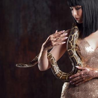 Schöne und geheimnisvolle brünette in einem goldenen kleid und mit einer schlange