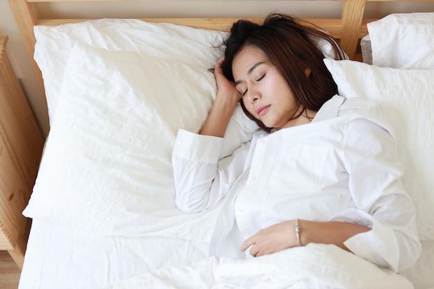 Schöne und gesunde asiatische frau, die auf weißem bett im schlafzimmer schläft