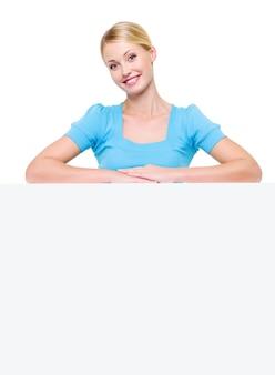 Schöne und glücklich lächelnde blonde frau unter der weißen plakatwand