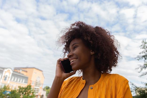 Schöne und glückliche afroamerikanerin auf der straße mit ihrem telefon