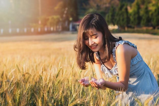 Schöne und glückliche asiatische frau, die das leben auf dem gerstengebiet bei sonnenuntergang genießt.