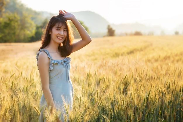 Schöne und glückliche asiatische frau im gerstenfeld bei sonnenuntergang.