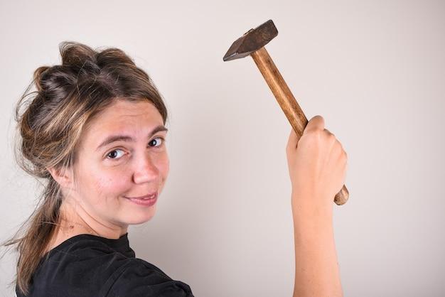 Schöne und glückliche frau, die einen hammer in ihren händen hält und schaut