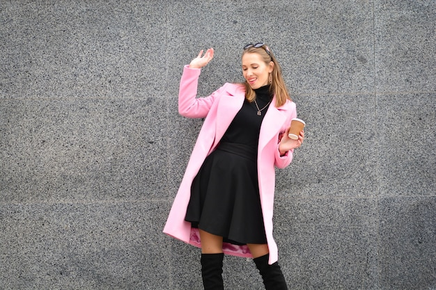 Schöne und glückliche frau im rosa mantel und in den kniehohen stiefeln, die mit kaffeetasse stehen und auf kamera auf granitwandhintergrund aufwerfen