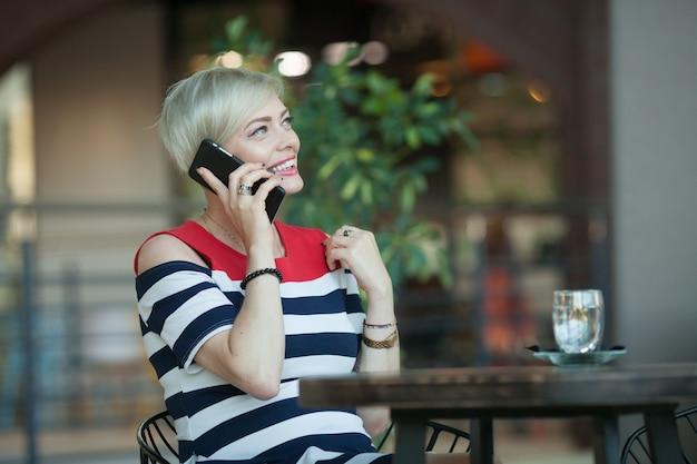 Schöne und glückliche frau mittleren alters, die auf handy spricht