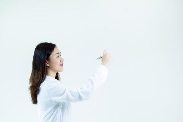 Schöne und intelligente asiatin im zufälligen weißen hemd unter verwendung eines stiftschreibens im leerstellenabschluß oben