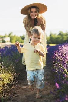 Schöne und junge frau mit ihrem süßen kleinen sohn auf einem lavendelfeld