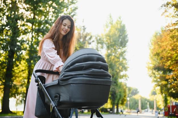 Schöne und junge frau, mutter und baby in einem kinderwagen, die im park spazieren gehen