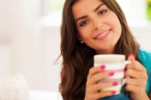Schöne und lächelnde frau mit einer tasse kaffee