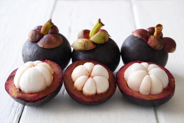 Schöne und leckere drei abgezogene mangostanfrüchten und drei mangostanfrüchten legen