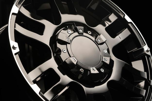 Schöne und leistungsstarke leichtmetallräder für suv. attrappe, lehrmodell, simulation. glänzende schwarze farbe und dunkler hintergrund. teuer und exklusiv.