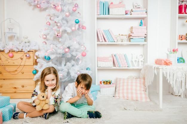Schöne und lustige kinder, die für kamera in einem kinderraum mit winterurlaubdekorationen aufwerfen.