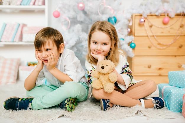 Schöne und lustige kinder, die für kamera in einem raum mit feiertagsdekorationen des neuen jahres aufwerfen.