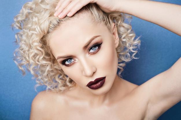 Schöne und modische frau mit erstaunlichen blauen augen, lockigem blondem haar und professionellem hellem make-up