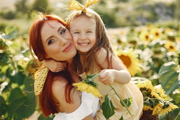 Schöne und nette familie auf einem gebiet mit sonnenblumen
