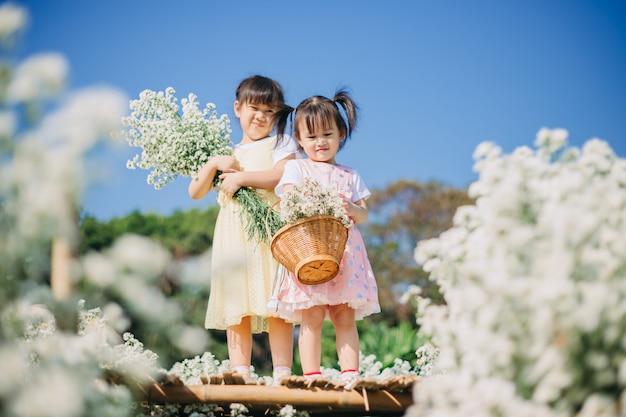 Schöne und nette kleinkinder, die zusammen im garten der weißen blumen spielen