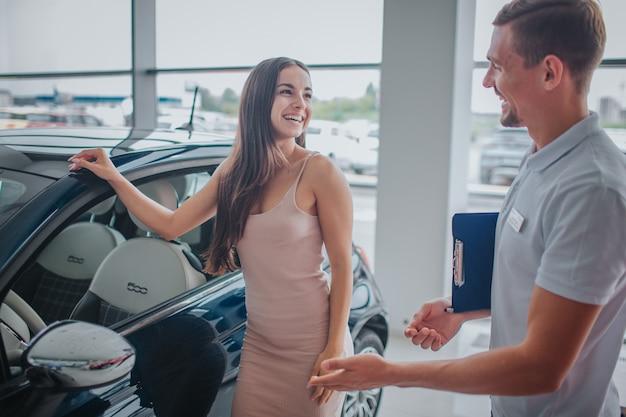 Schöne und positive junge frau steht neben schwarzem auto und hält hand drauf. sie sieht den verkäufer an und lächelt. junge männer sehen sie an und lächeln auch. er zeigt auf das auto.