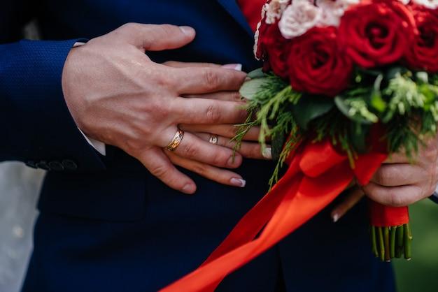 Schöne und raffinierte hochzeitsstrauß-nahaufnahme hält die braut in ihren händen neben dem bräutigam. hochzeitsstrauß und ringe.
