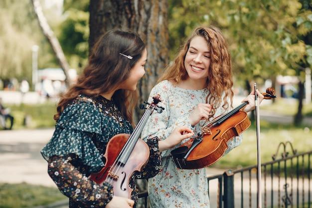 Schöne und romantische mädchen in einem park mit einer violine