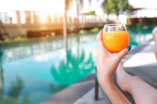 Schöne und sexy frauenhände genießen feiertagsferien mit orangensaft im swimmingpool