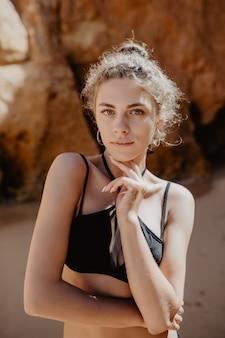 Schöne und sexy hübsche frau am strand mit felsen