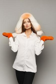 Schöne und sexy junge brünette modellfrau mit hellem make-up, in einer weißen pelzmütze, in den orangefarbenen pelzhandschuhen und in einer weißen bluse