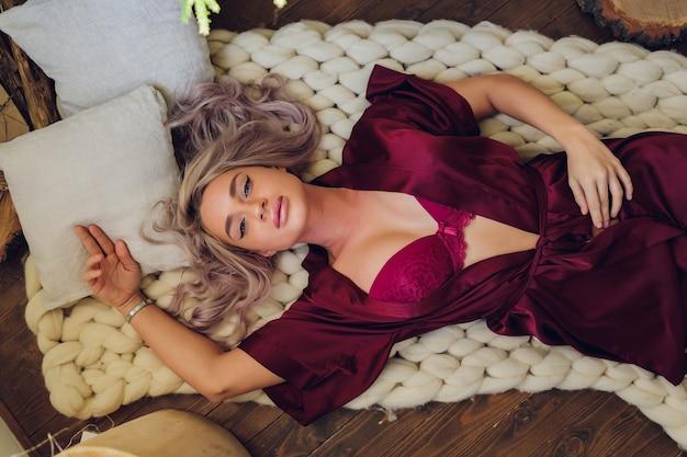 Schöne und sexy junge erwachsene kaukasische frau mit honigblonden haaren, die dessous in einem boudoir-schlafzimmer tragen