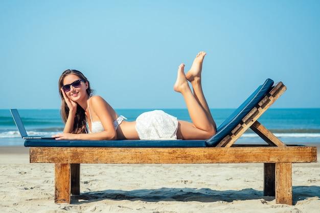 Schöne und sexy junge frau liegt und ruht auf einem liegestuhl mit einem laptop des meeres. freiberuflerin mit laptop im resort