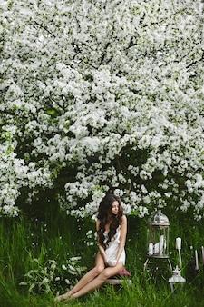 Schöne und sexy vorbildliche brünette frau mit perfektem körper in stilvollen dessous mit einer weißen taube in ihren händen, die unter dem blühenden baum am grünen wald aufwirft