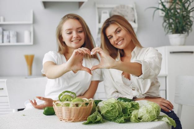 Schöne und sportliche frauen in einer küche mit gemüse