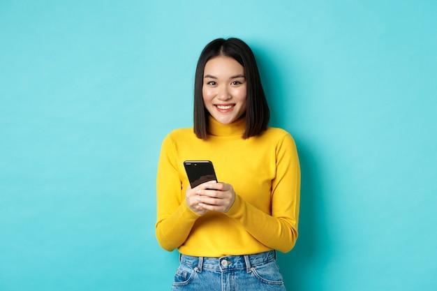 Schöne und stilvolle asiatische frau, die online auf dem handy einkauft und auf blauem hintergrund steht