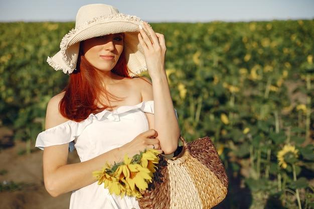 Schöne und stilvolle frau auf einem gebiet mit sonnenblumen