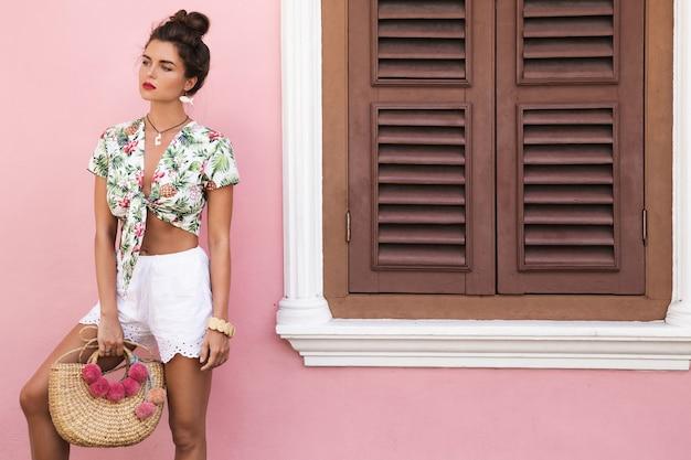 Schöne und stilvolle frau, die sommerkleidung trägt, posiert neben dem haus mit einer rosa wand