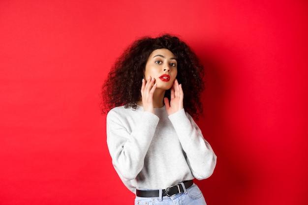 Schöne und stilvolle lockige frau mit roten lippen, die das perfekte junge gesicht berührt und sinnlich in die kamera schaut, vor rotem hintergrund stehend
