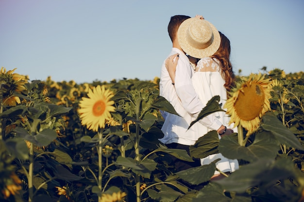 Schöne und stilvolle paare auf einem gebiet mit sonnenblumen