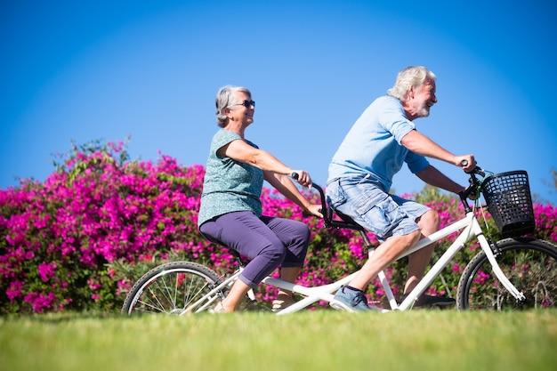 Schöne und süße paare von reifen und alten frauen und männern, die zusammen ein doppelfahrrad in einem grünen park mit rosa blumen im hintergrund fahren. aktiver senior, der spaß mit tandem hat