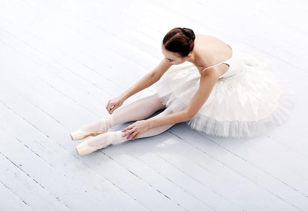 Schöne und wunderschöne ballerina, die auf dem boden sitzt