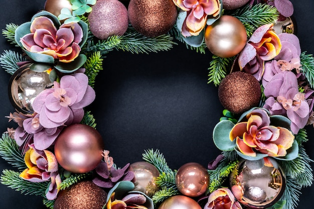 Schöne ungewöhnliche weihnachtskranzdekoration auf schwarzem. wohnung lag mit copyspace in der mitte