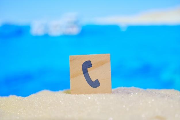 Schöne unscharfe ansicht des strandes mit sand und tedefon-zeichen als symbol für anruf und kommunikation, bestellung einer tour, reisen.