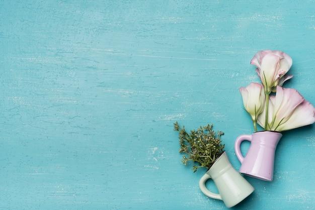 Schöne vasen auf blauem strukturiertem hölzernem hintergrund