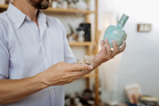 Schöne vasen. bärtiger handwerker, der sich inspiriert und kreativ fühlt, während er schöne vasen herstellt
