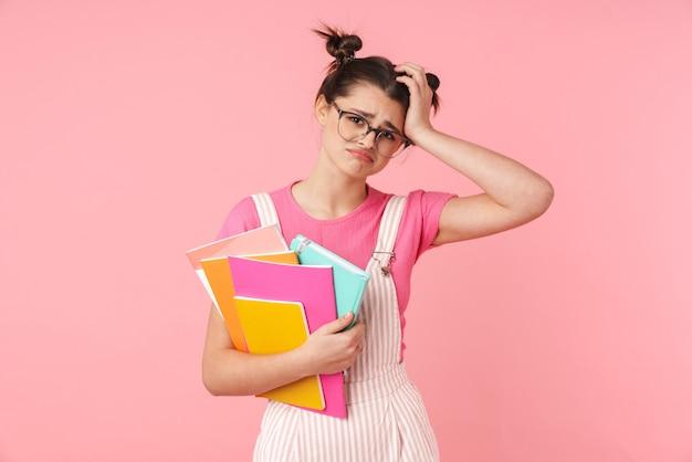 Schöne verärgerte teenager-mädchen stehen isoliert, mit lehrbüchern