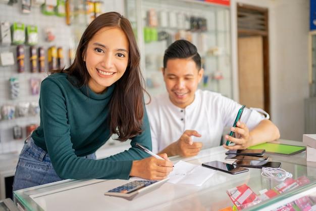Schöne verkäuferin lächelt, während sie mit einem mann arbeitet, der warenbriefpapier mit notizen überprüft...